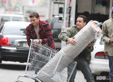 "Actors Bryan Greenberg and Victor Rasuk wrestling with some Jean Shop fabric in the upcoming HBO series ""How to Make It in America."" Jean Shop owner Eric Goldstein served as a technical writer for the show that debuts February 14. Look out for his cameo in the first season."