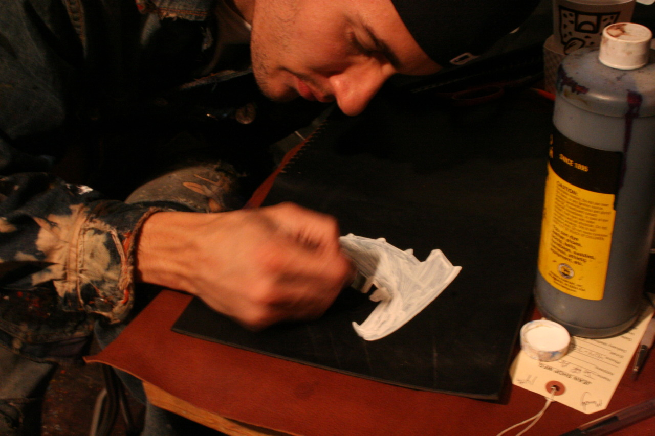 Alex doing a custom paint job on one of our leather ipad cases.