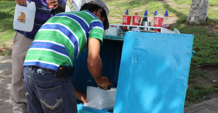 A vendor shaving the ice for granizados dos leches.