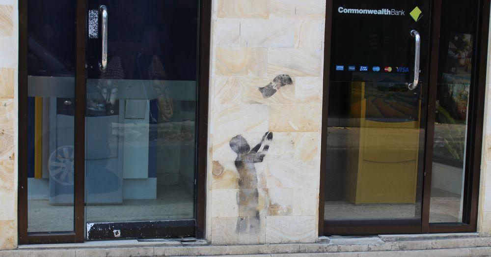 Banksy-style art on a roadside ATM. Ubud Village.