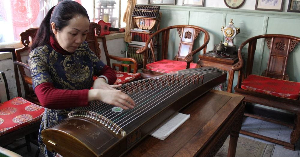 Woman playing a Guzheng.