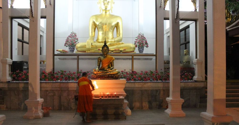 A monk lighting the offerings at Wat Saket.