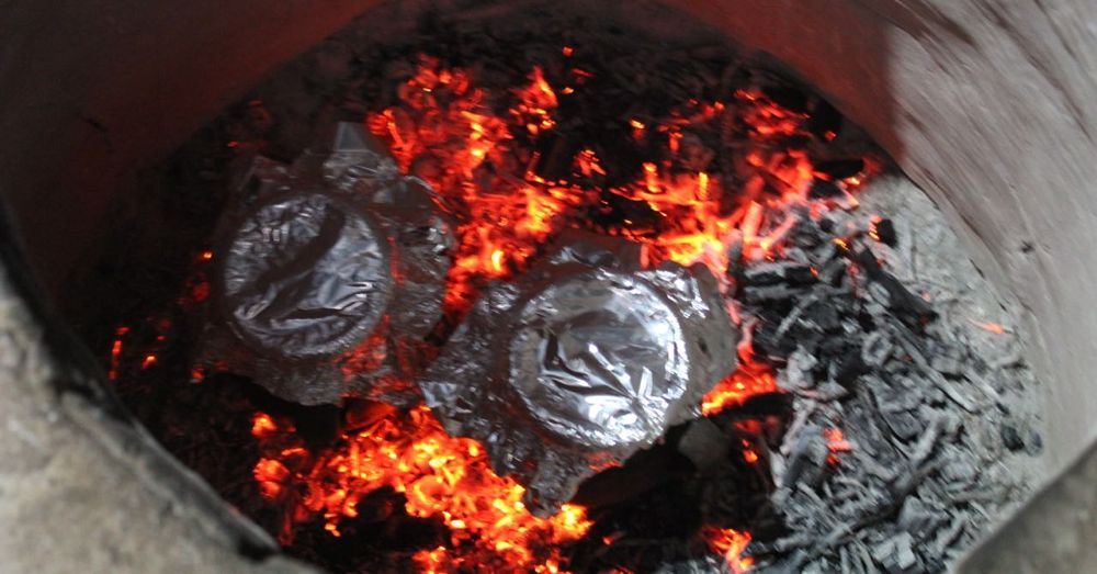 Foil-topped clay pots cooking in the tandoor.