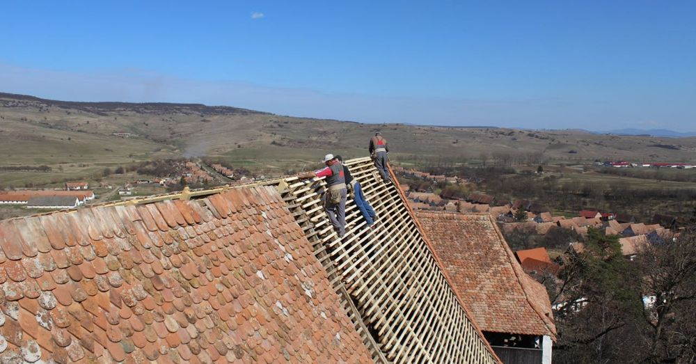Volunteers repairing the roof of the White Church in Viscri.