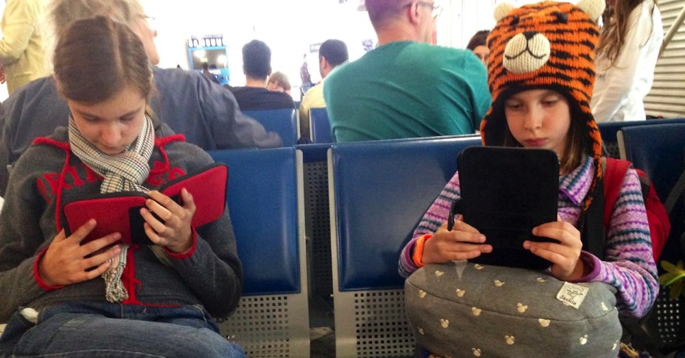 Reading on our kindles while waiting for another flight.
