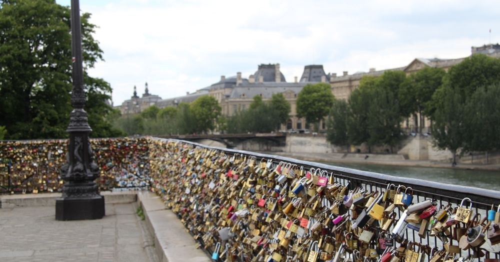 Love Locks on the New Bridge in Paris. The Pont des Arts (the old lock bridge) is in the background.