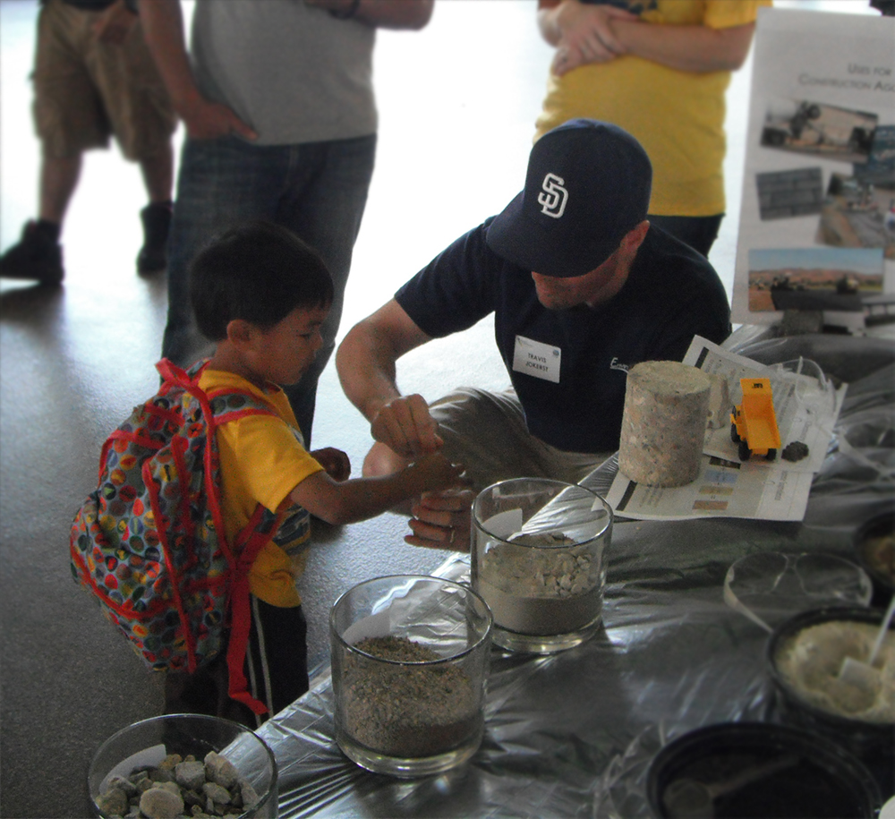 Travis Jokerst from EnviroMINE, Inc. helping a young boy mix concrete.
