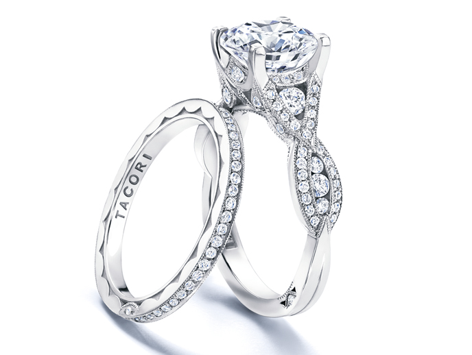 "Ribbon Collection by Tacori    The expression ""when two become one"" is a love story personified with the Ribbon collection. In these stunning designs, two ribbons twist together on separate diamond-studded paths to create the foundation of the ring, which band into ""one"" at the sparkling center of the diamond."