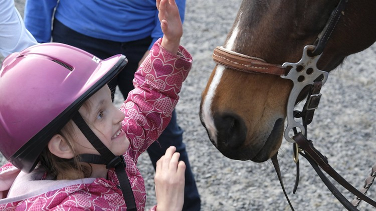 Kileigh Palmer, a student at Possum Elementary, gives her horse a pet after dismounting at the Yellow Springs Riding Center Thursday. Bill Lackey/Staff