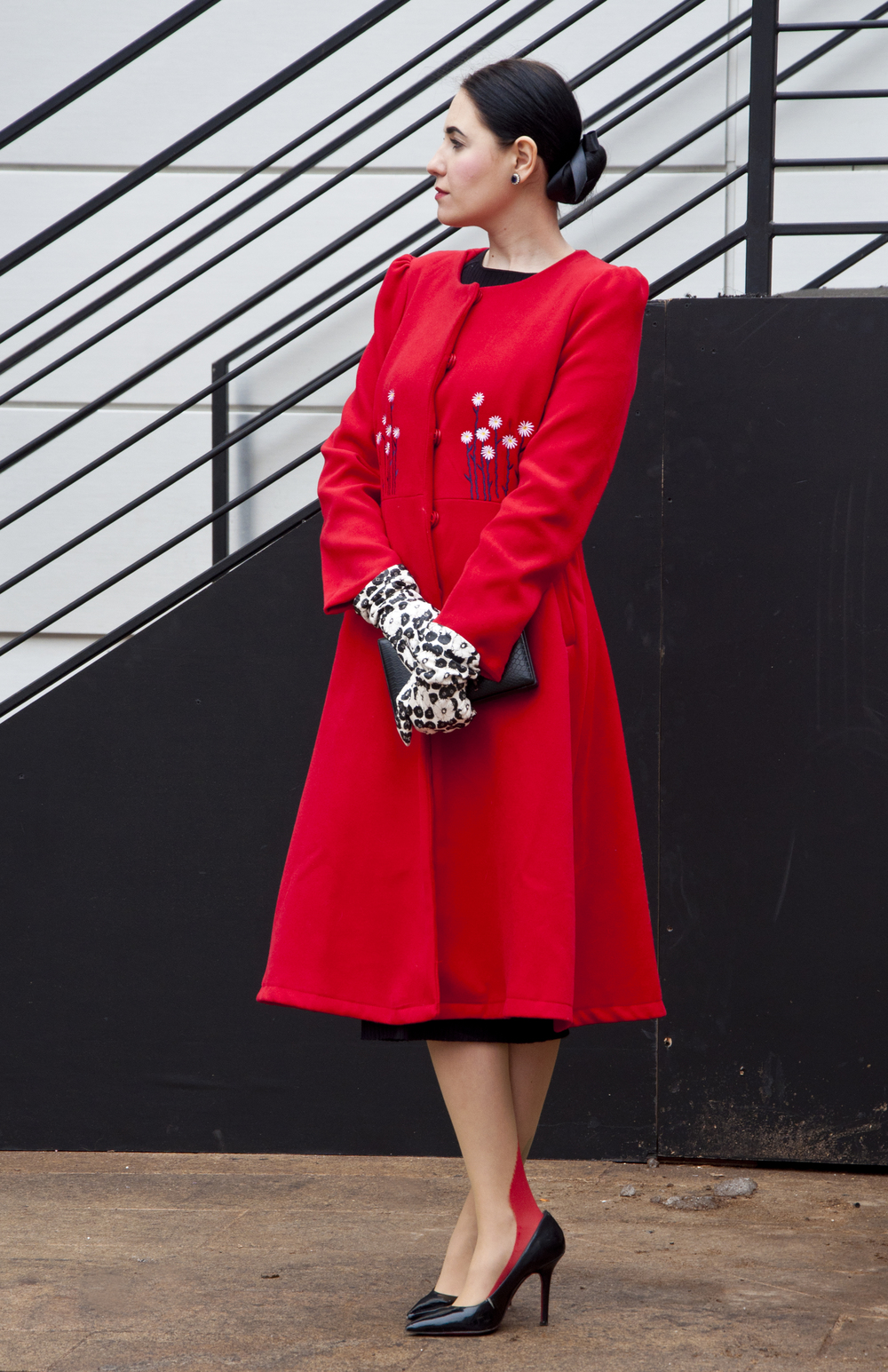 Nora Kobrenik wearing a coat by Vika Gazinskaya Loubs, paired with a vintage clutch