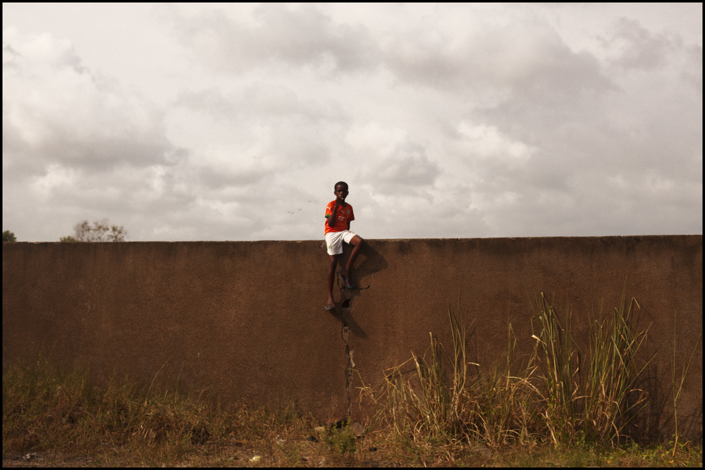 2-4-2012 a young boy sits on a high wall (Grand-Bassam, Ivory Coast).jpg
