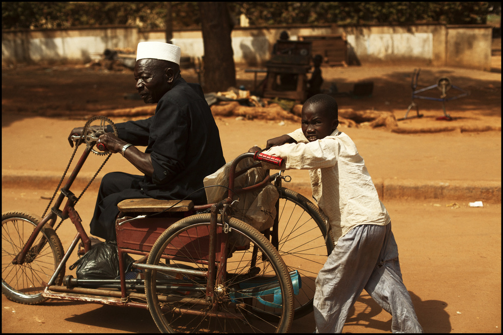 1-30-2012 a young boy pushes his grandfather (Yamassoukro, Ivory Coast).jpg