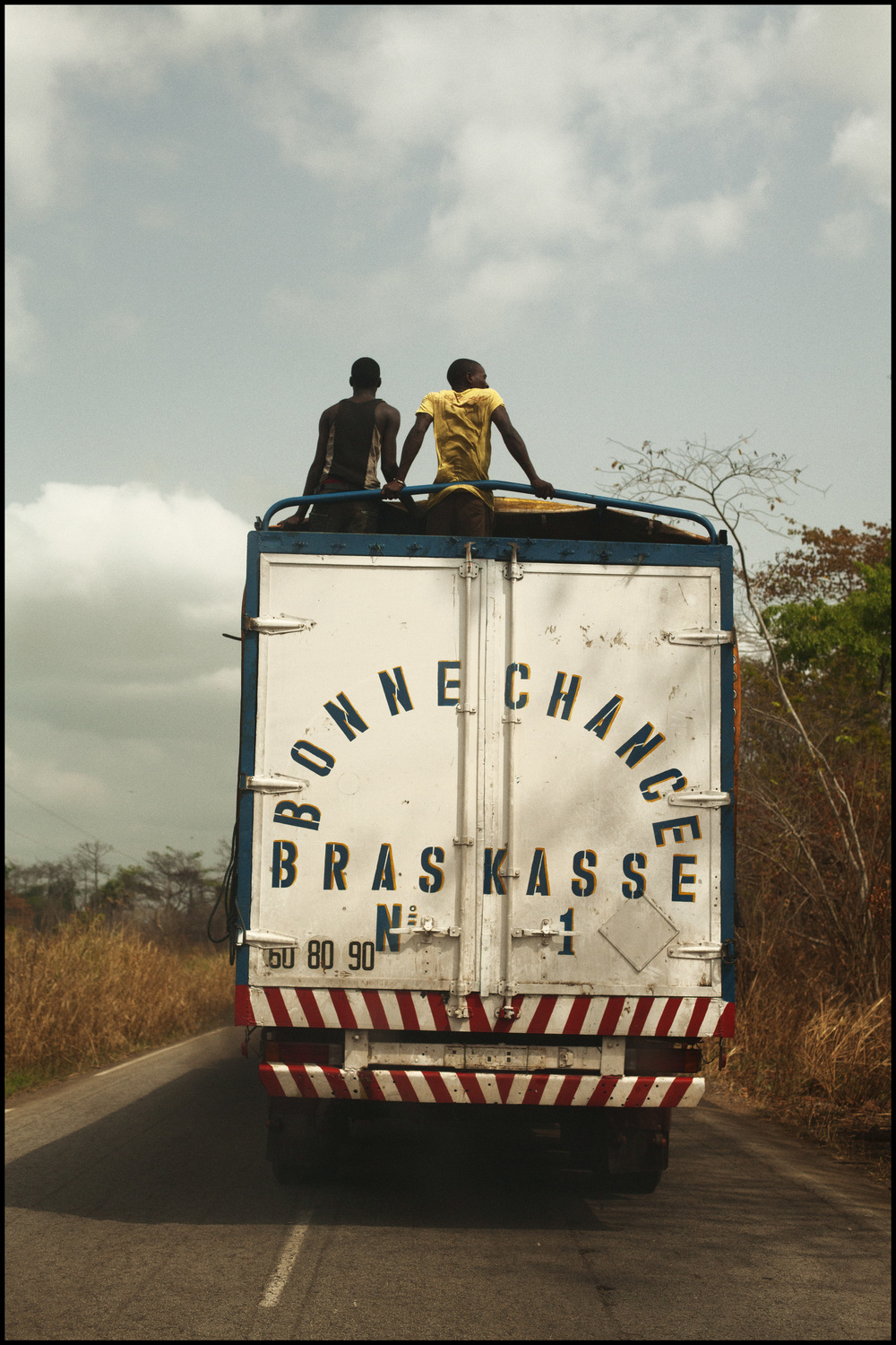 1-30-2012 two young men ride on top of a semi (between Abidjan and Yamassoukro, Ivory Coast).jpg