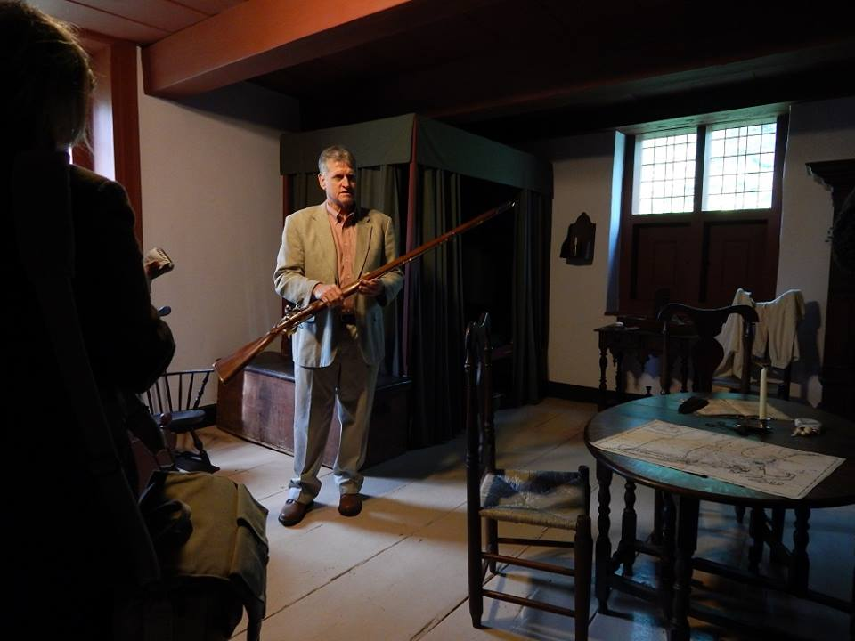 Bill Weldon holding a replica musket in the Jean Hasbrouck House