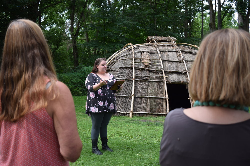 "Programming Associate Amber Neilson leads the ""In Her Words"" Women's History Tour in front of the wigwam"