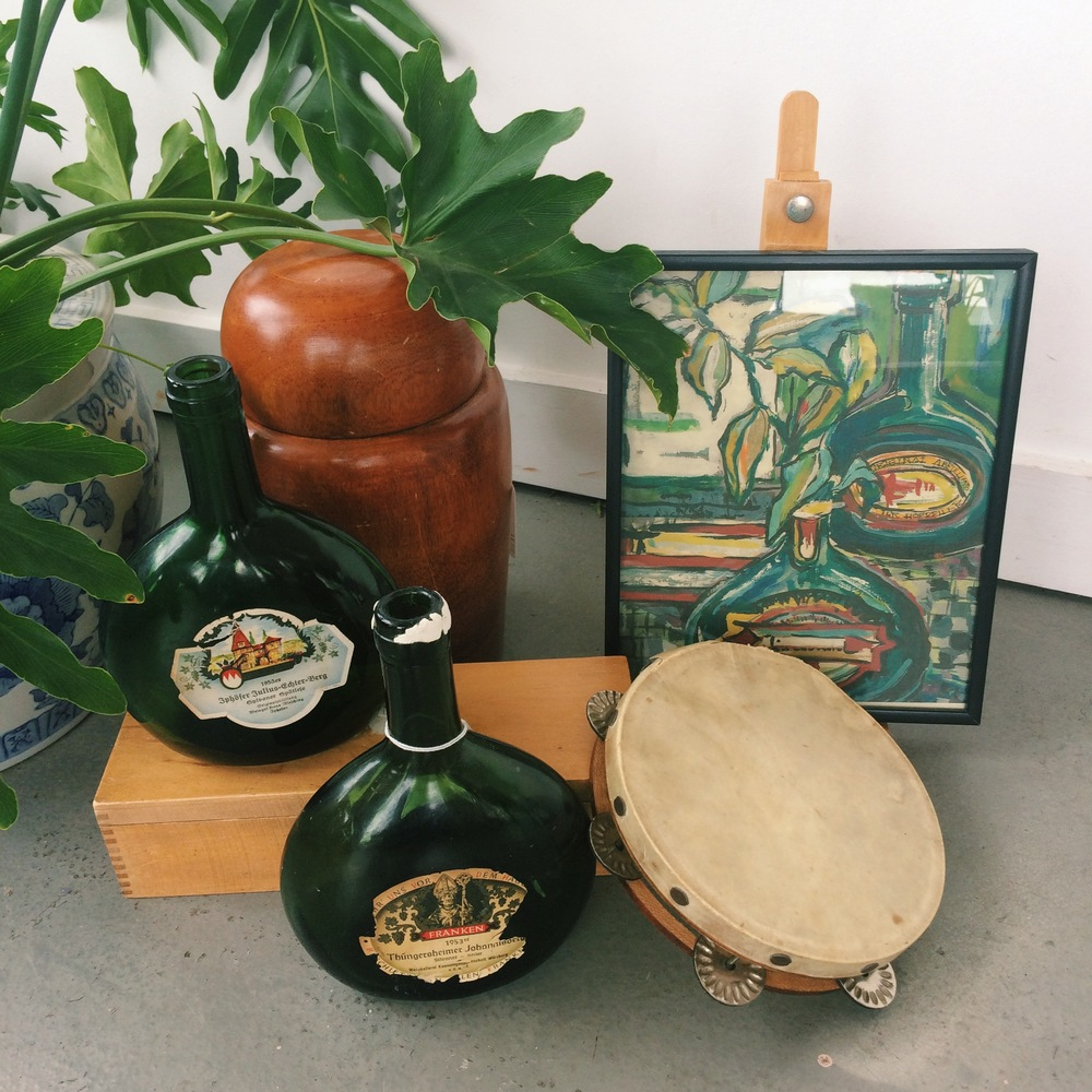 Vintage bottles, teak container, vintage tambourine, and bottle print