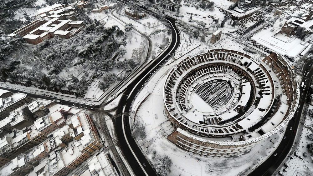 Roman Colosseum, Italy    Now here's a scene you don't see every day—the Colosseum from above while under a blanket of snow. ( via )