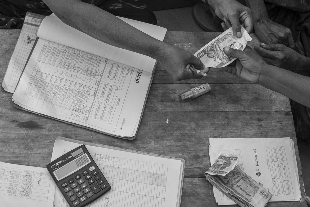 Members of Pact's micro-banking program WORTH balance their accounts in Myanmar's dry zone.
