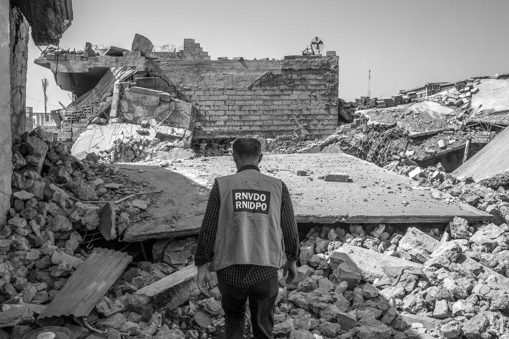 A member of an Iraqi partner organization surveys rubble in West Mosul.