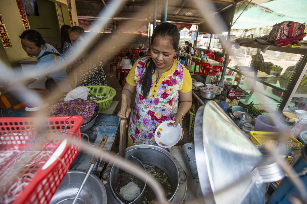 A WORTH member cooks lunch at her small business in Cambodia.