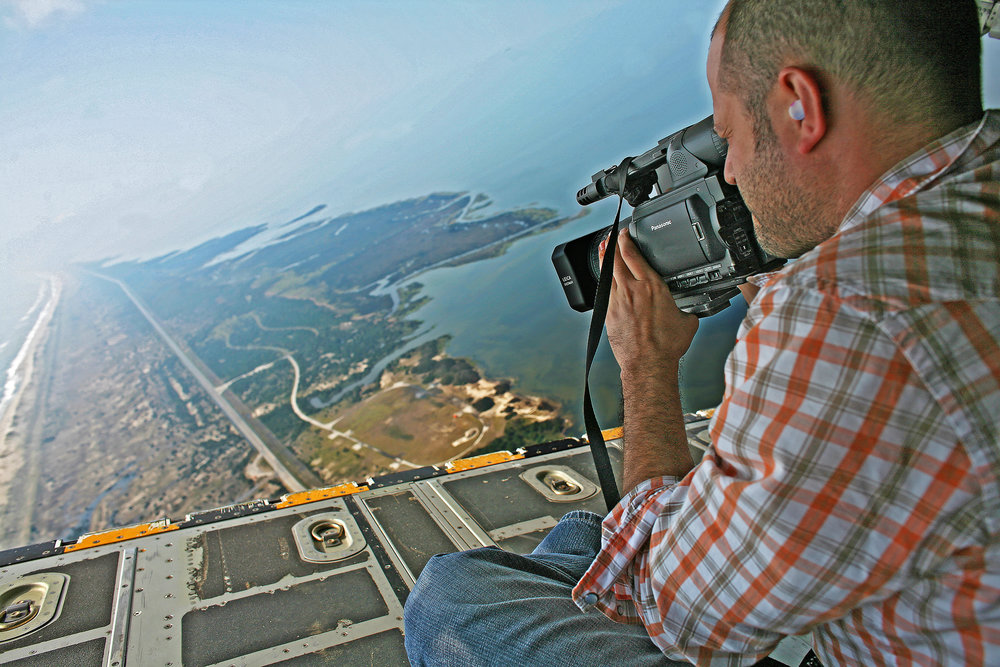 Brian shooting hurricane damage from the cargo hatch of a Coast Guard C-130 aircraft