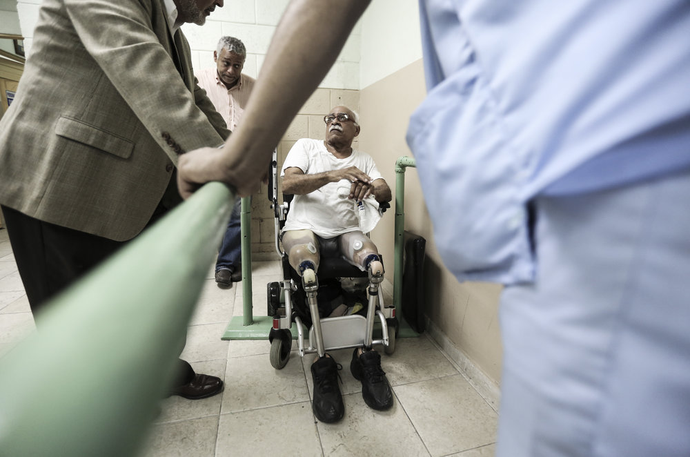 A patient converses with two docters as his son looks on before attempting to walk on prothetic limbs for the first time.