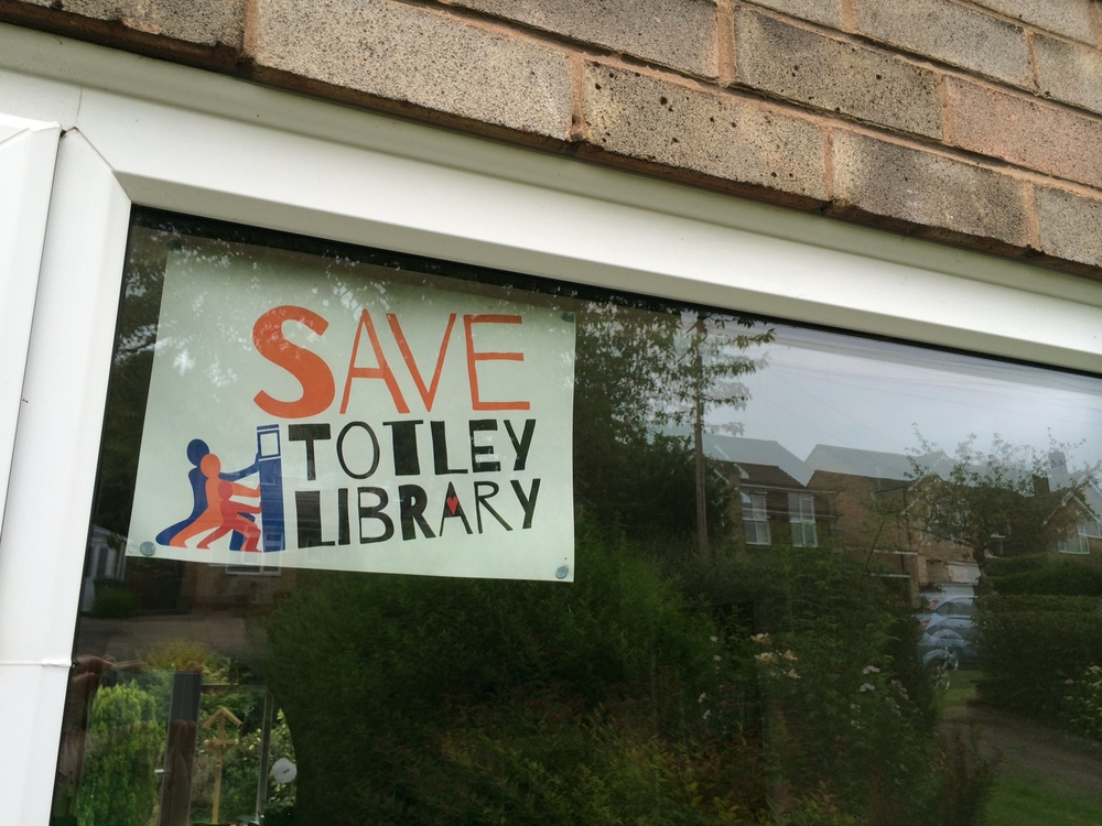 Save Totley Library campaign logo in house window.
