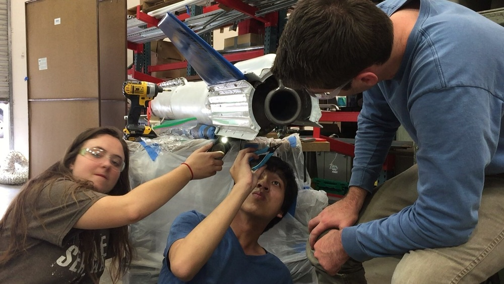 Nikolai Dorbritz, Kevin Hoo, and Zoe Warp work on the integration between the fins, boattail, and engine thrust struts.