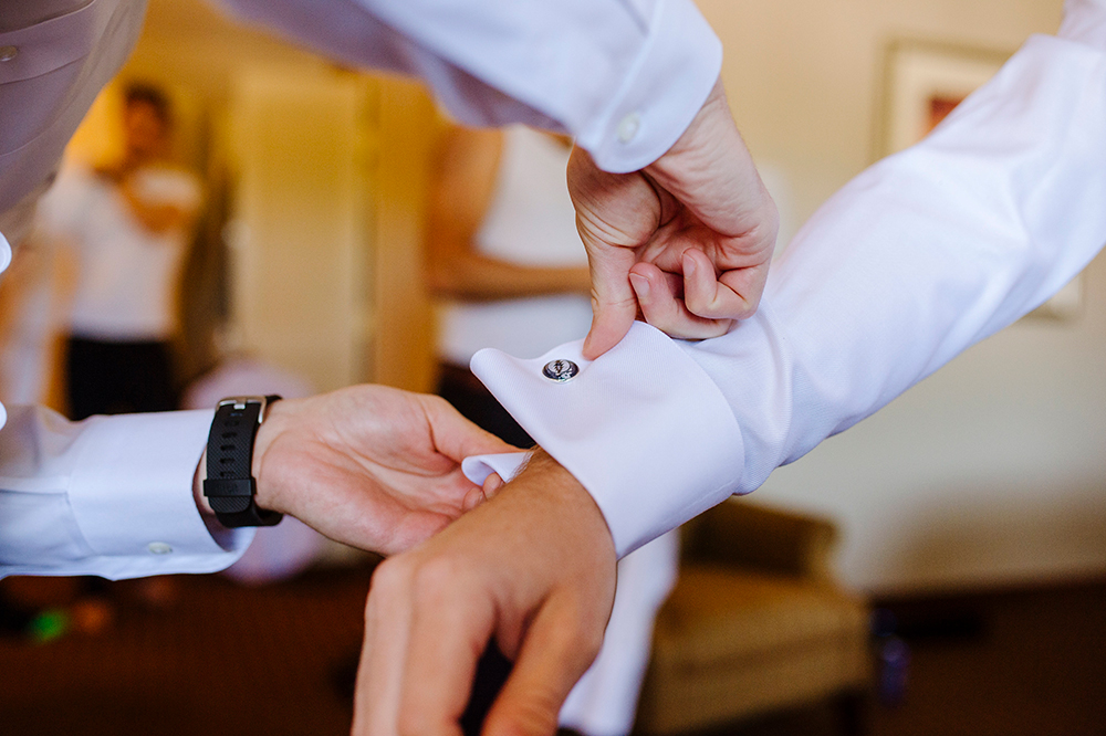 Groomsman helping groom get dressed before wedding