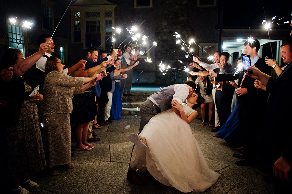 Groom dips bride during sparkler exit