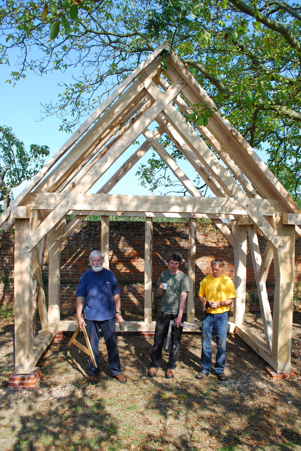 Our three instructors, Laurie Smith, Joel Hendry, and William Clement Smith, standing under the completed timber frame.