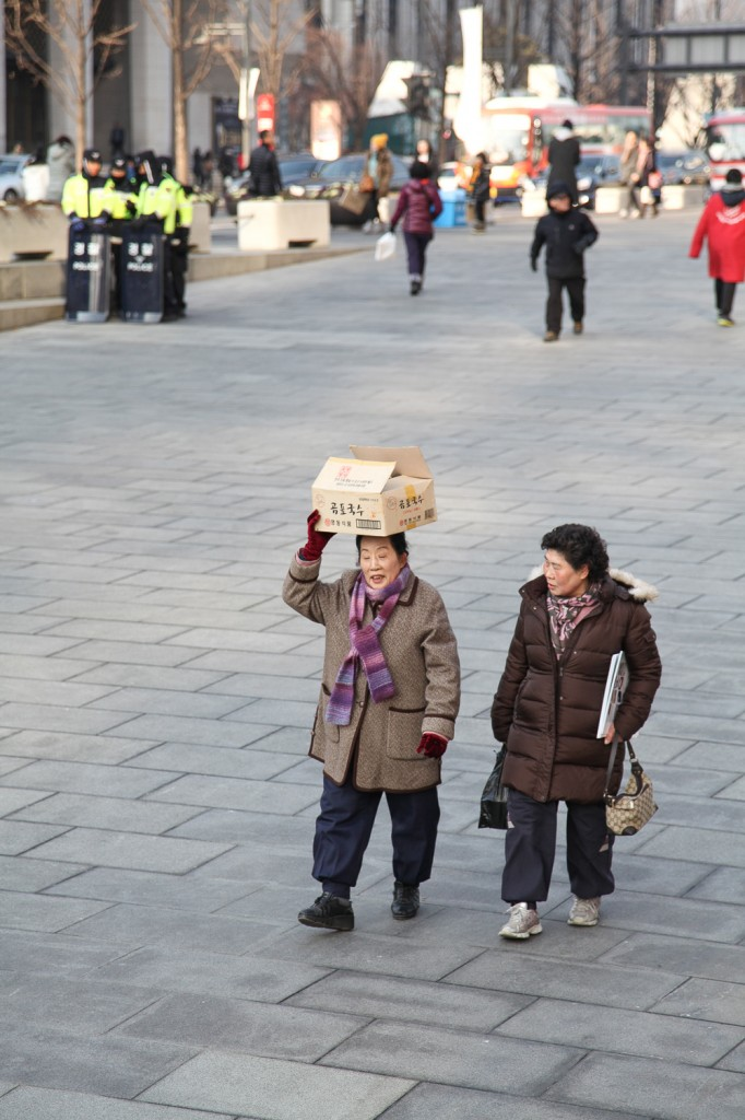 Two women walking and talking. Not the first time seeing people carry boxes on their head.