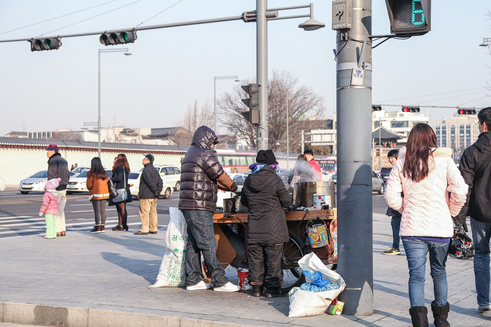 Street food sold on a triangular island surrounded by roads. Target customers: pedestrians on the way or from Gyeongbokgung Palace.