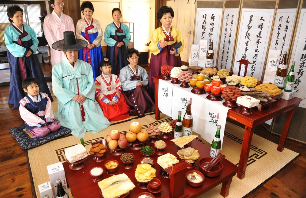Charye. Family wearing hanbok, facing the wooden table of prepared foods.  (Photo  :  Tagstory )
