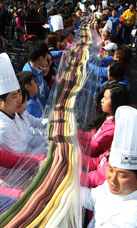 Veteran rice cake makers and participants holding the five colors of garaetteok on Garaetteok Day in Insadong (The Korea Times)