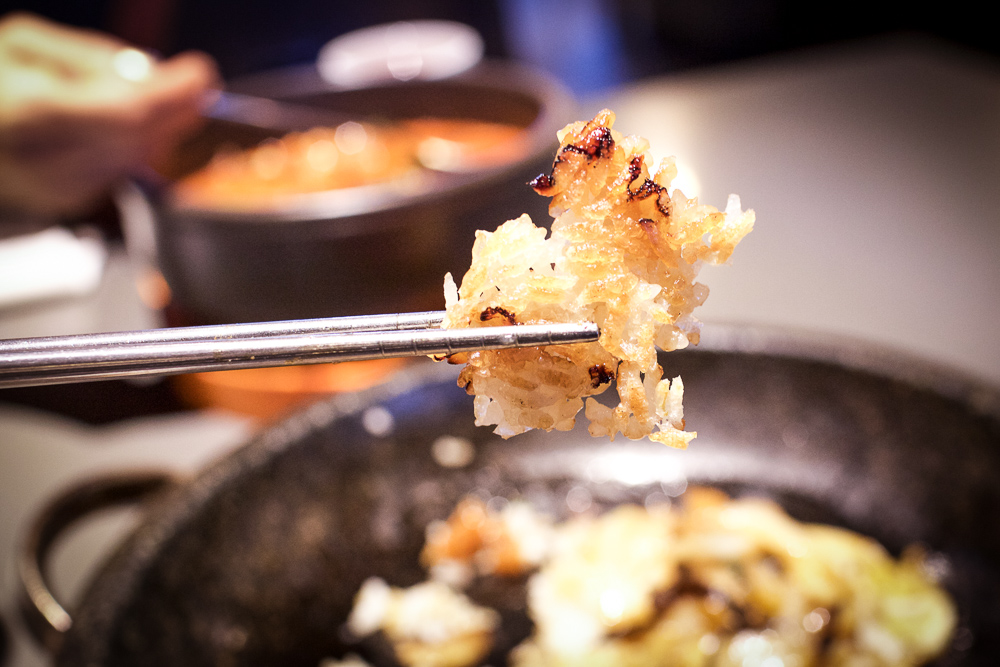 Picking at the toasted layer of white rice from Bibimbap Grilled Eel