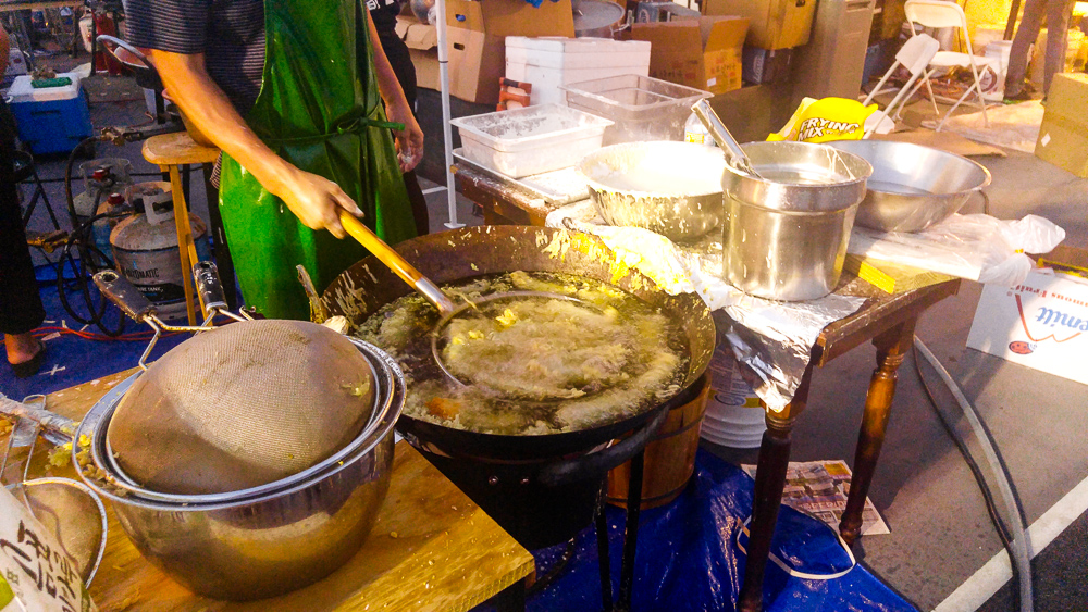 Vendor deep-frying sea cucumbers