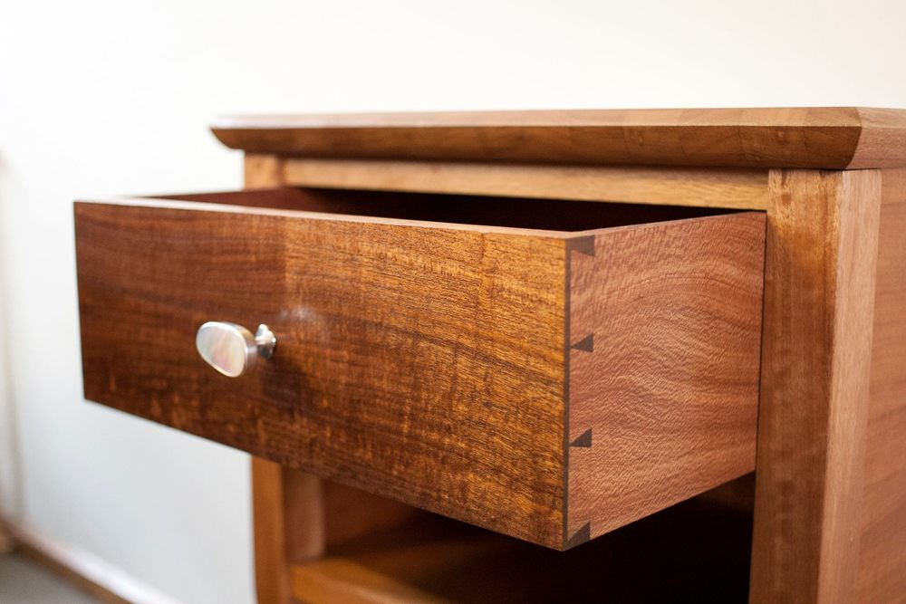 A delicate bedside table made from solid Queensland maple, northern silky oak and Tasmanian blackwood, along with a silver and mother of pearl drawer pull. French polish and wax finish.