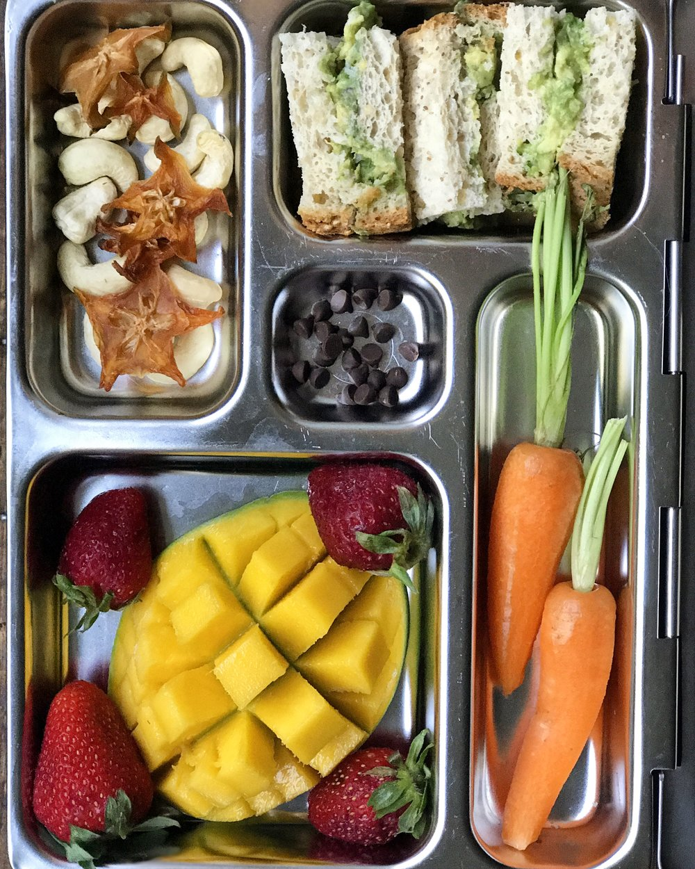 Lunch box contents: raw cashews & dried starfruit,   Chickpea & Avocado Salad  on gluten free bread, mango and strawberries, carrot,  chocolate chips . Lunch box by  Planet Box .