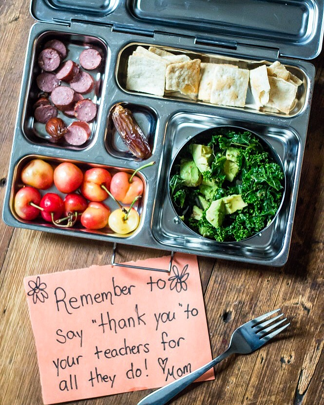 Lunch box contents: sausage coins,   grain-free crackers , massaged kale and avocado salad, cherries, pitted date. Lunch box by  Planet Box .