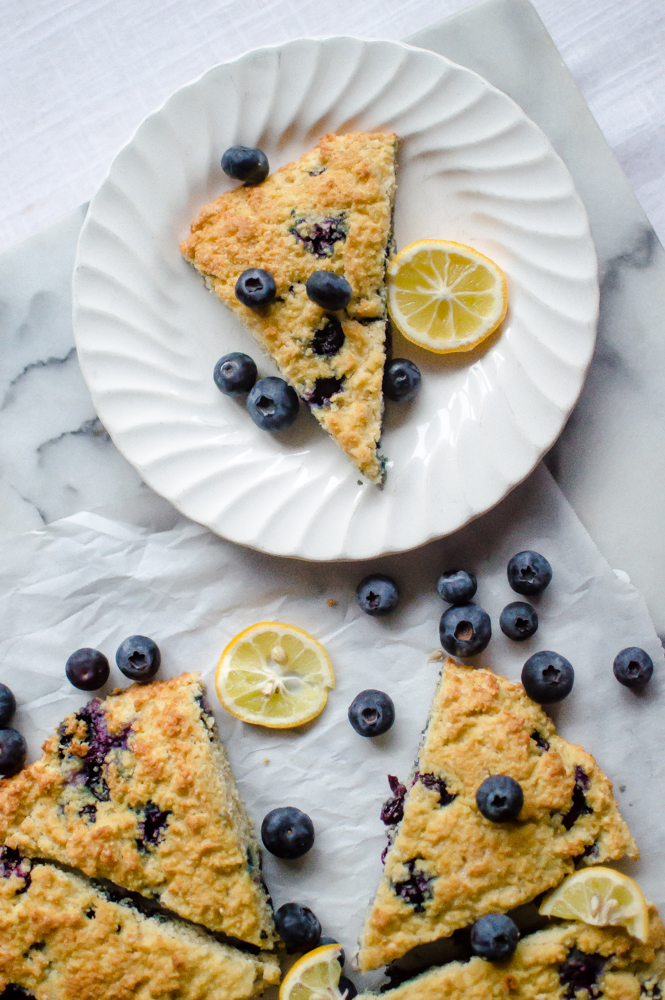 Paleo Lemon Blueberry Scones are the perfect, tasty,tangy breakfast treat for to dunk in your coffee on a sleepy weekend morning at home or to grab on the go to be enjoyed in your car (because that's how it happens sometimes). Kid-approved over and over again, these wedges of yum are Paleo, dairy-free, gluten free, and grain-free! #paleobaking #paleoscones #glutenfreebaking #glutenfreescones