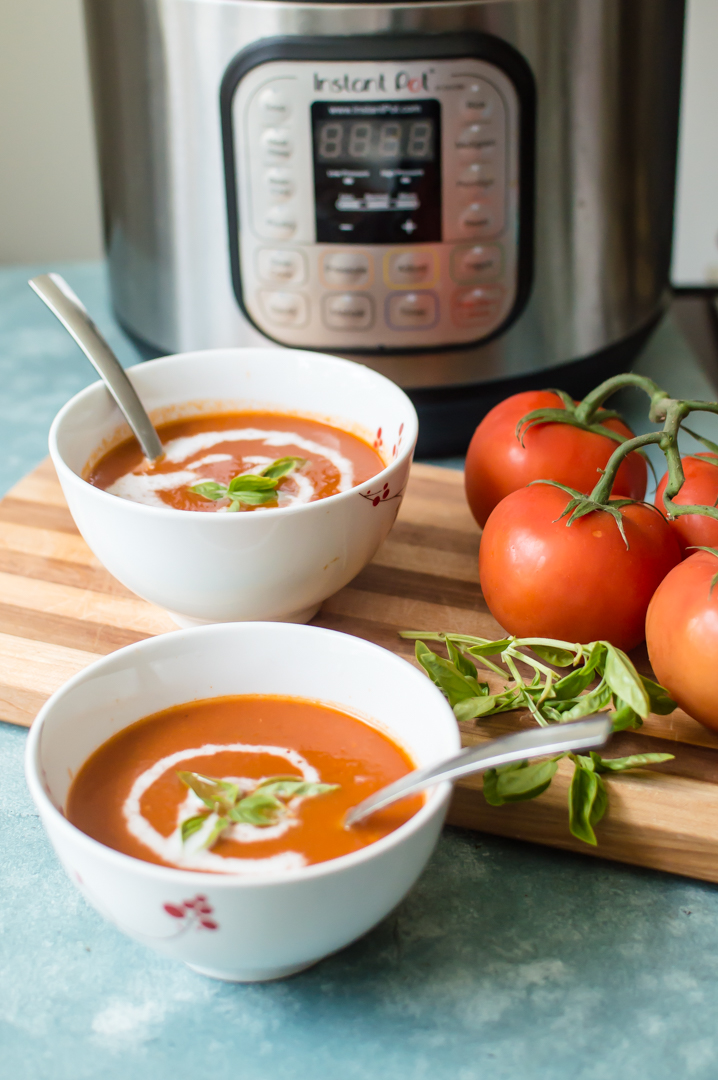 Instant Pot Creamy Tomato Basil Soup is going to give you the warm fuzzies all over! Full of that classic flavor we all grew up on (and probably dunked a grilled cheese or two in), this dairy-free, Paleo, Whole30 complaint soup is made with ease in your Instant Pot in  a matter of minutes and puts the processed canned stuff of our youth to shame. #whole30soup #instantpotsoup #paleotomatosoup