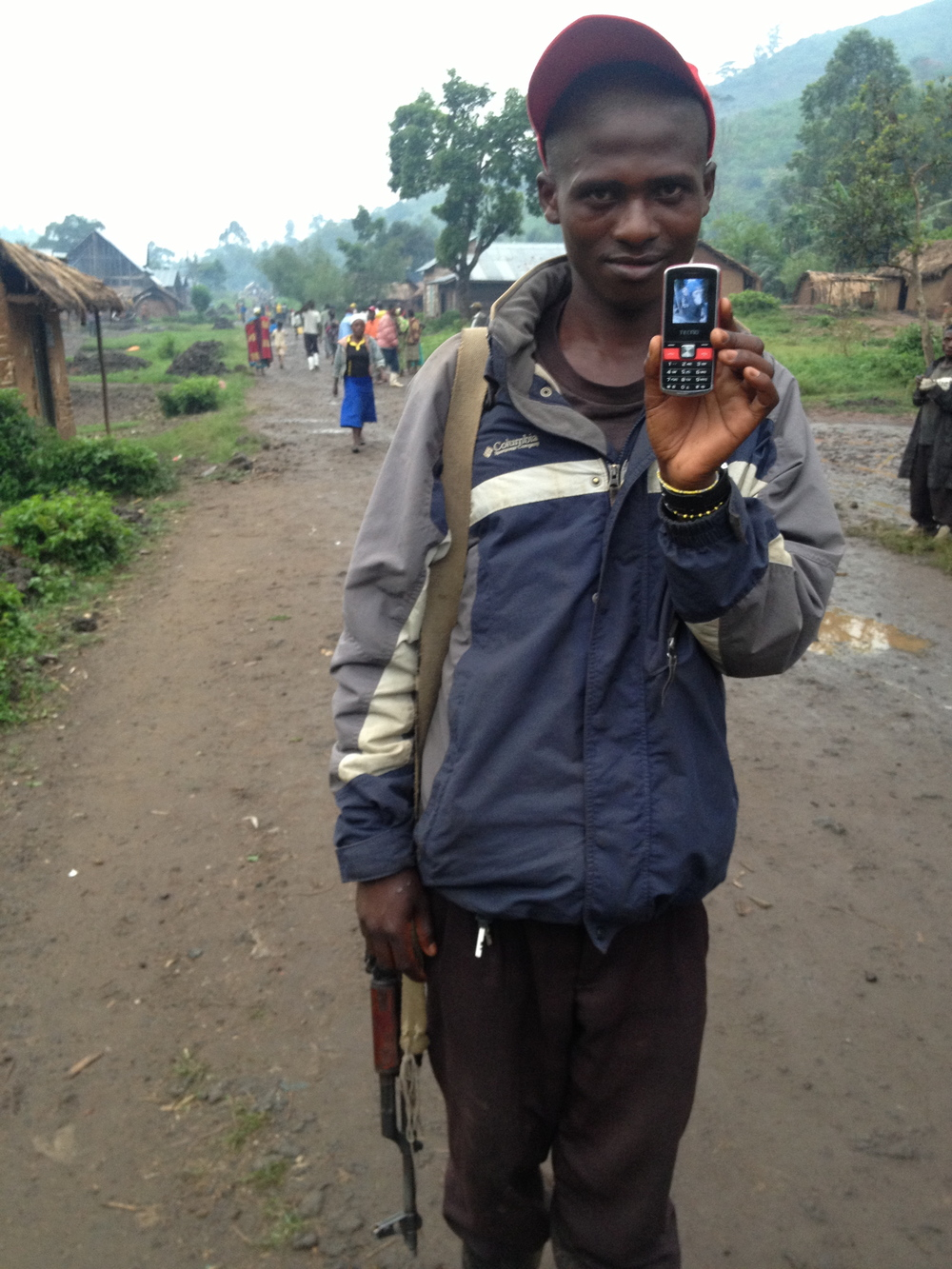 This young boy holds his gun and a photo of a chimpanzee he wants me to buy from him. The bizarre moments in life…
