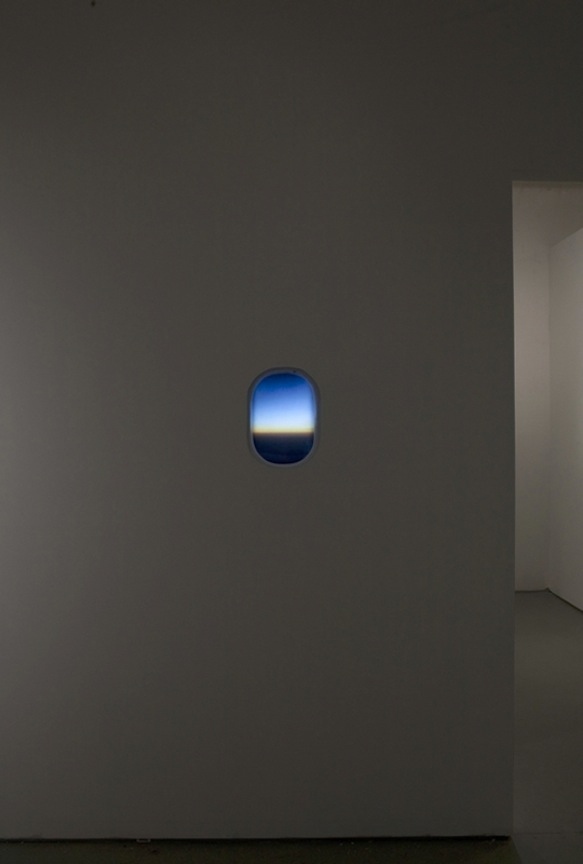 Your house is the last before the infinite    2011 Fujitran, plexiglas, Aerbus window, bulbs, ballast and wall 15 x 9 x 4 in / 38.1 x 22.9 x 10.2 cm