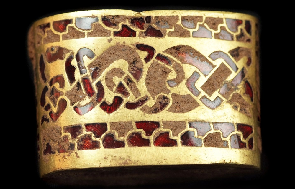 Anglo-Saxon sword hilt fitting, circa 8th Century AD. The piece contains beautiful inlaid deep red garnet gemstones.