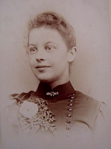 Alluring Victorian lady with a horseshoe brooch pin adorning her collar.