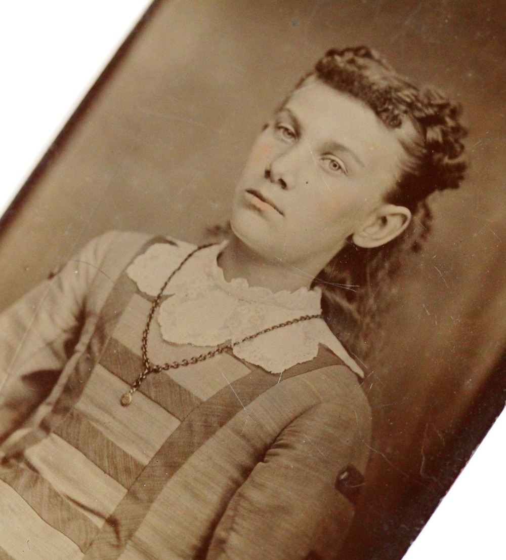 Victorian era tintype of a young girl wearing a thickly chained dainty pendant locket.