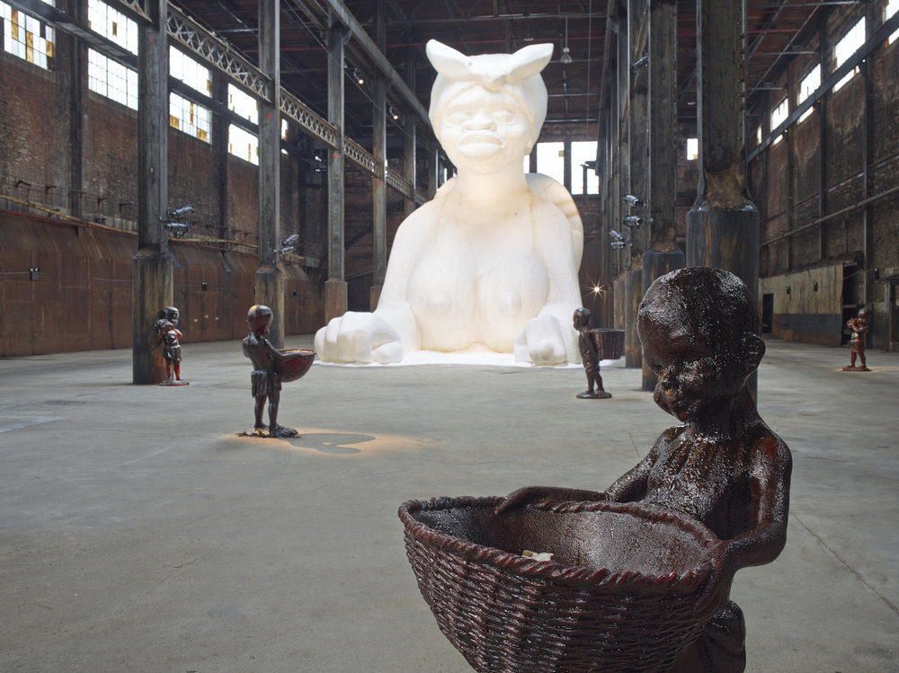 Kara Walker,  At the behest of Creative Time Kara E. Walker has confected: A Subtlety, or the Marvelous Sugar Baby, an Homage to the unpaid and overworked Artisans who have refined our Sweet tastes from the cane fields to the Kitchens of the New World on the Occasion of the demolition of the Domino Sugar Refining Plant . Domino Sugar Refinery ,  Brooklyn, NY, 2014. Photo: Jason Wyche