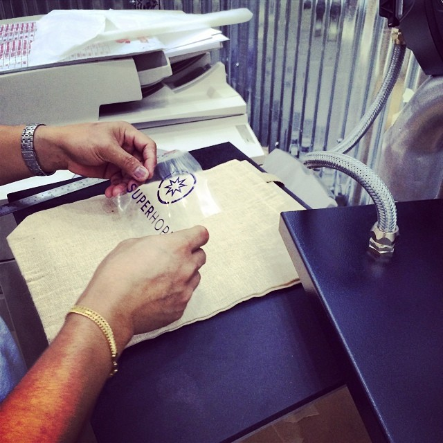 The incredible team at @toilandtinker heat transferring our logo on our cool @soriginalcreations canvas bags #thinksuper #superhope #canvas #bag #star #love #hope #friends