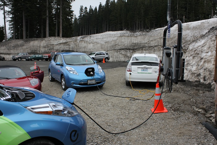 A posse of electric cars including two Nissan LEAFs (blue), two Tesla Roadsters (one not pictured) and a converted plug-in Prius gather around the charging stations to fill up.